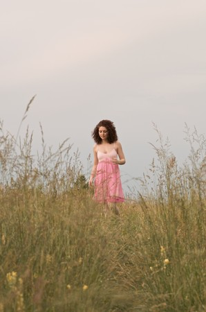 A young woman wearing a pink dress is smiling and standing in a field. Vertical shot. photo
