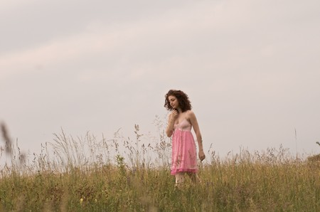 A young woman wearing a pink dress is walking in a field. Horizontal shot. photo