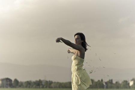 An attractive young woman holds out handfuls of grass which she lets go in the wind.  Horizontal shot. photo