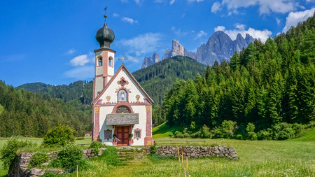 Chapel in a green field and mountains
