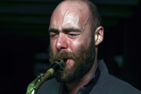 internships: young jazz player with beard playing alto sax in the studio