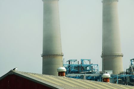 monterey: A power plant at Moss Landing, California, at the head of Monterey Bay. a seagull is perched on the nearby rooftop in the foreground.