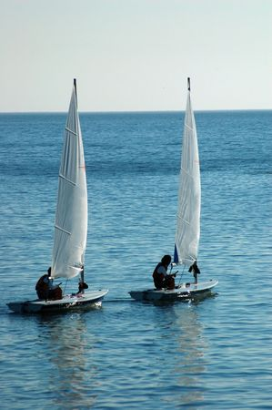 a couple of sail dinghies out in the ocean photo