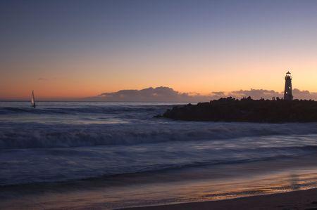 Lighthouse at Santa Cruz, California at sunset with a windsurfer.