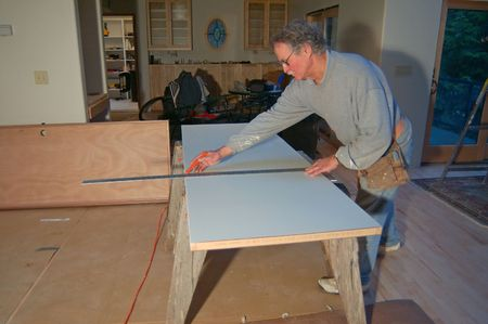 A man measuring some boards down to saw them photo