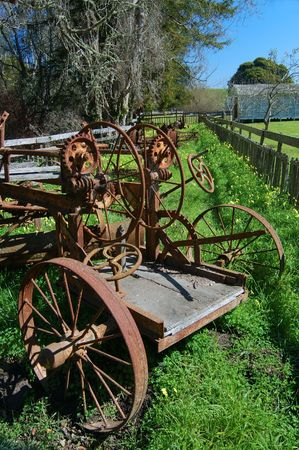 implements: rusty farm implements in a green pasture Stock Photo