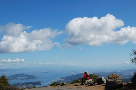 Mountain Biker rests near the East Summit of Mt. Tamalpais, California and admires the view of San Francisco Bay