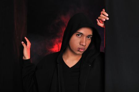 A guy with a black hood standing in front of backlit smoke photo