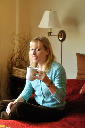 woman enjoying a cup of morning coffee in her bedroom photo
