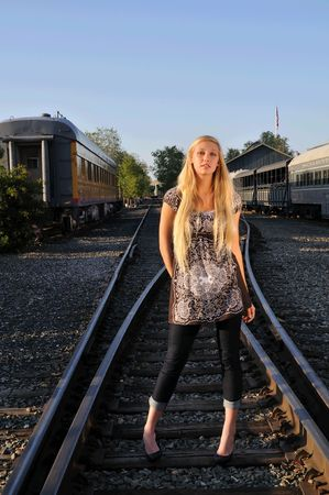 young blond woman posing for the camera on a railroad track photo