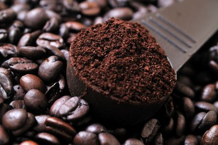 closeup of coffee beans and a scooper with ground coffee