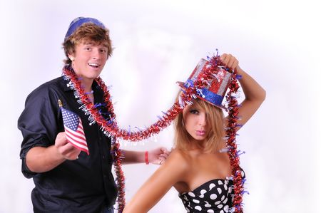 Patriotic couple dressed up with uncle Sam hats and US flag paraphanilia for the 4th of July photo