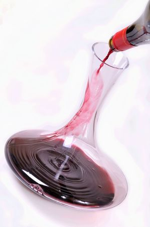 poured: red wine being poured into a decanter