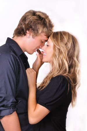 eating chocolate: young happy couple sharing chocolate candy Stock Photo