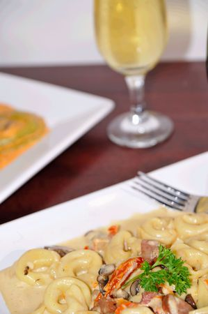 pinot: gourmet tortellini pasta with a glass of wine in the background