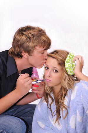 nursing bottle: boyfriend taking care of his sick girlfriend Stock Photo