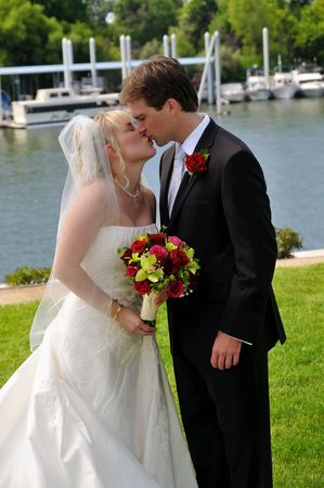 bride and groom on the lawn kissing after their wedding photo