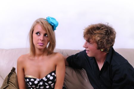 intrusive: man and a woman on couch, young woman looking annoyed at his presence Stock Photo