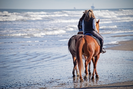woman and horse:  Riding Horses on the Beach  Stock Photo