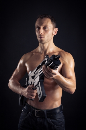 sexy army: Powerful young man with assault rifle Stock Photo