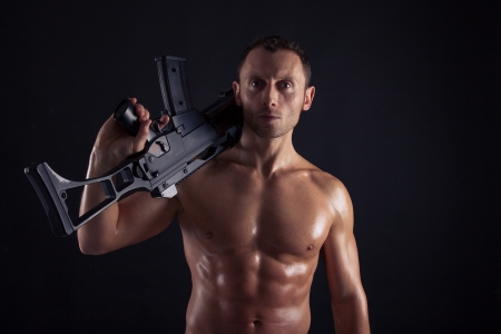 man holding gun: Powerful young man with assault rifle Stock Photo