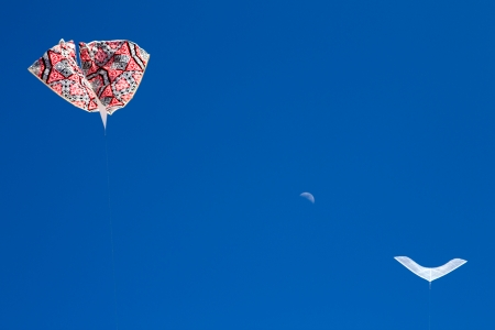 two kites flying in the sky with the moon in the background Stock Photo