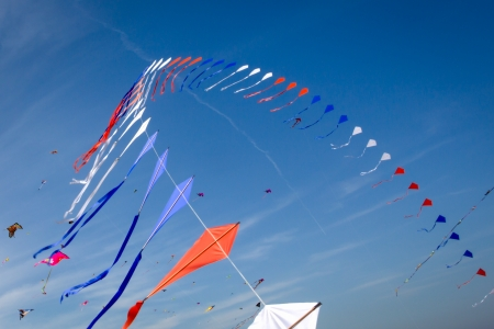 many kites flying in the blue sky photo