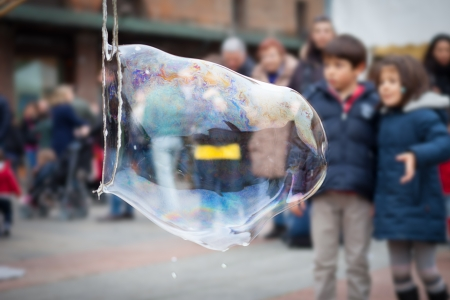 child in the background looks at a giant soap bubble