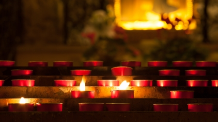 candles with flame inside a church in Italy