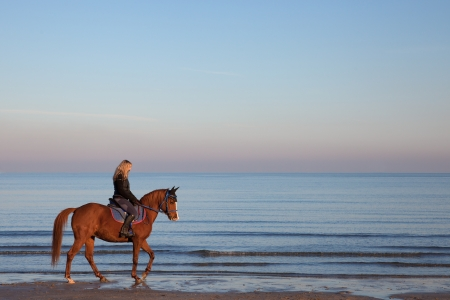 girl riding a horse on the beach Stock Photo
