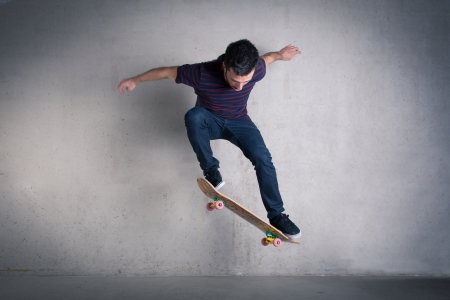 Skateboarder doing a skateboard trick - ollie - against concrete wall.