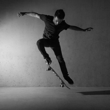 Skateboarder doing a skateboard trick - ollie - against concrete wall.