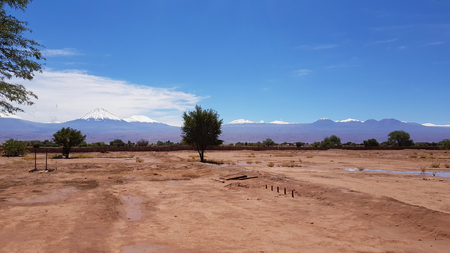 The arid and desolate landscape of the Atacama Desert and the peaks of the snowy volcanoes of the Andes cordillera in the background