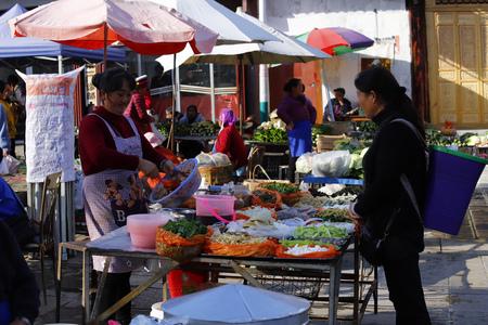 Zhoucheng village, Yunnan, China - November, 2018. Zhoucheng village market stall selling vegetables, Dali, Yunnan, China Editorial