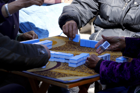 People playing Chinese dominoes in a street in the village of Shigu, Yunnan, China