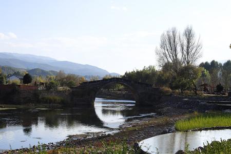 An ancient stone bridge (Yujin Bridge) cross the Heihui River on the Ancient Tea Horse Road in the village of Shaxi, Yunnan, China