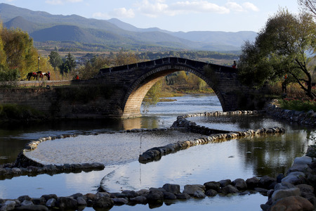 A stone bridge (Yujin Bridge) cross the Heihui River on the Ancient Tea Horse Road in the village of Shaxi in the province of Yunnan, China