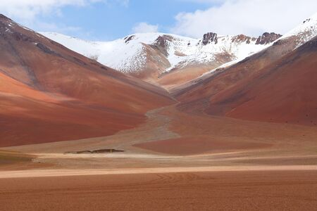 Landscape of the Bolivian highlands. Desert landscape of the Andean plateau of Bolivia with the peaks of the snow-capped volcanoes of the Andes
