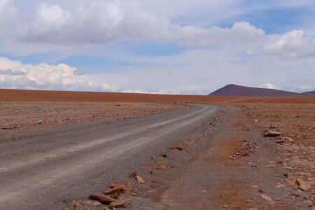 A road in the landscape of the Bolivian highlands. Desert landscape of the Andean plateau of Bolivia with the peaks of the snow-capped volcanoes of the Andes