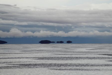 Mirages on the water? Surreal effects in the Salar de Uyuni flooded after the rains, Bolivia. Clouds reflected in the water of the Salar de Uyuni, Bolivia