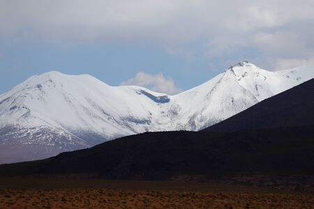 Snow-capped volcanoes and desert landscapes in the highlands of Bolivia. Andean landscapes of the Bolivia Plateau Stock Photo