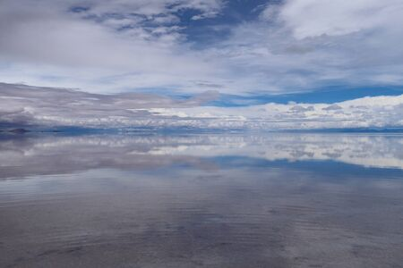 The Salar de Uyuni flooded after the rains, Bolivia. Clouds reflected in the water of the Salar de Uyuni, Bolivia 写真素材