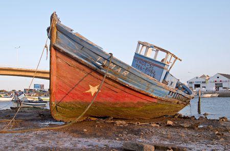 Stranded old boat in the sea channel of Tavira, Algarve, Portugal