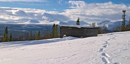 sweden winter: Winter panorama from Lifttoppen, footprints on snow, trees, clouds and a shelter, V�l�dalen, Sweden