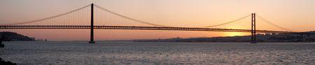 Panorama of bridge 25 de Abril on river Tagus at sunset, Lisbon, Portugal