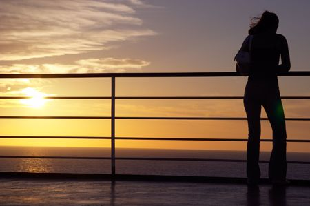 Girl black silhouette and red sunset on a ferry