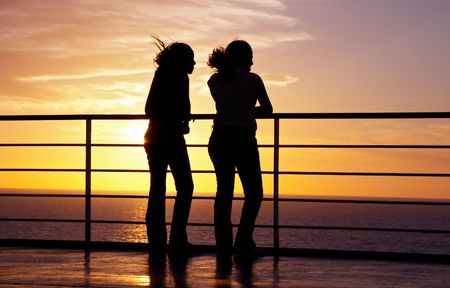 Two girls black silhouette and red sunset on a ferry