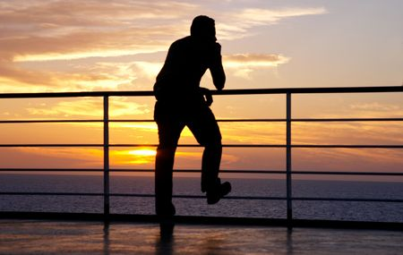 Thinking man silhouette and red sunset on a ferry