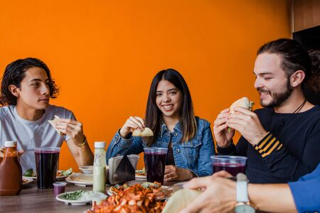 Mexican people eating Tacos al Pastor in a Taqueria in Mexico