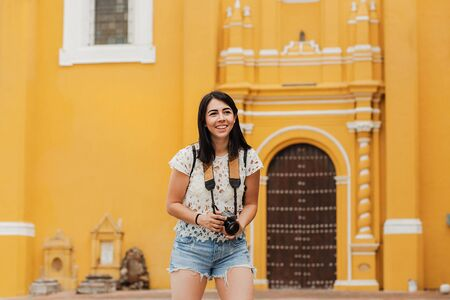 Traveling Latin Woman tourist backpackers holding a camera photo in Mexico city 写真素材